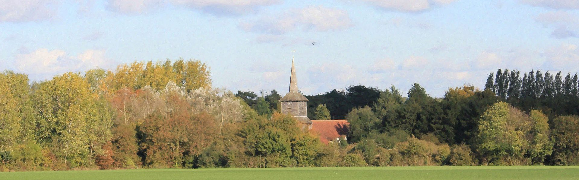 An autumn view across open farm land towards the bell tower of St Laurence church.