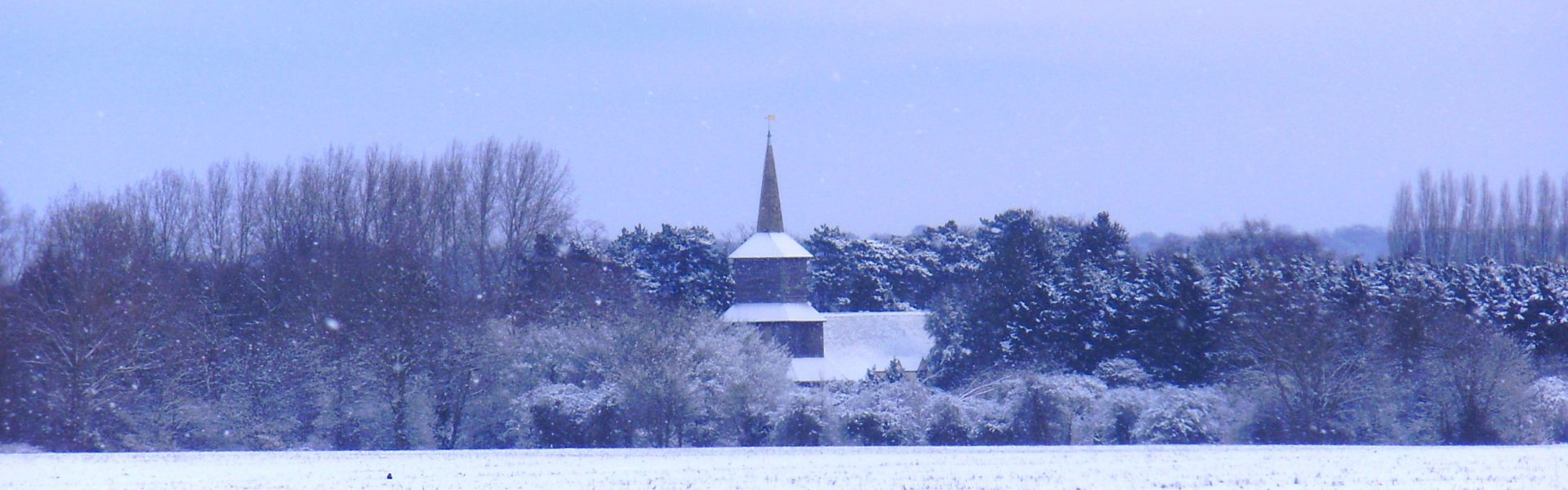 A snowy view across open farm land towards the bell tower of St Laurence church.